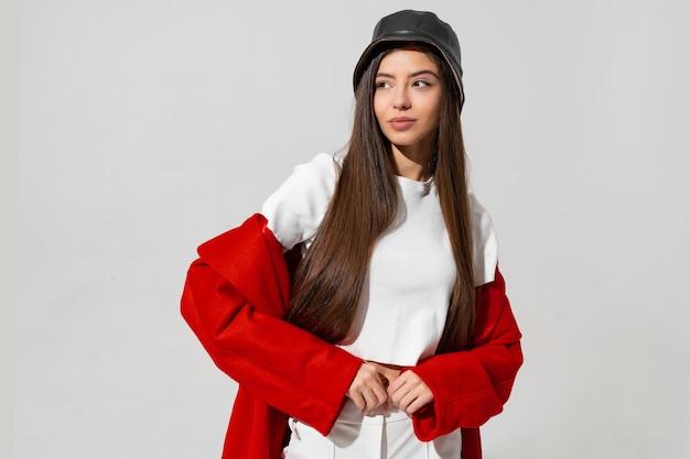 Ładna dziewczyna w czarnym kapeluszu i czerwonym płaszczu uniosła ręce i trzymając czapkę w studio na białej ścianie