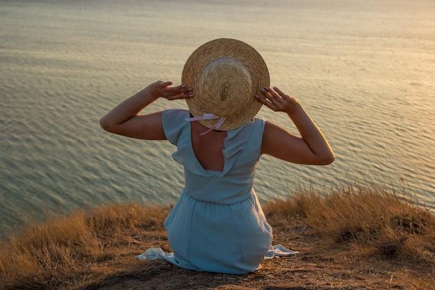 Ładna dziewczyna w długiej niebieskiej sukience i słomkowym kapeluszu siedzi na wysokim klifie nad morzem. młoda kobieta trzyma kapelusz z białą wstążką rękami przez wiatr nad brzegiem spokojnego morza o zachodzie słońca.