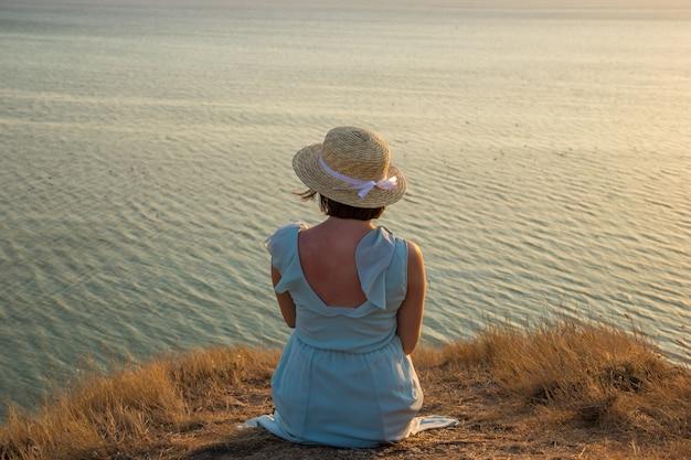 Ładna dziewczyna w długiej niebieskiej sukience i słomkowym kapeluszu siedzi na wysokim klifie nad morzem. młoda piękna kobieta w kapeluszu z białą wstążką oglądając zachód słońca nad brzegiem spokojnego morza.