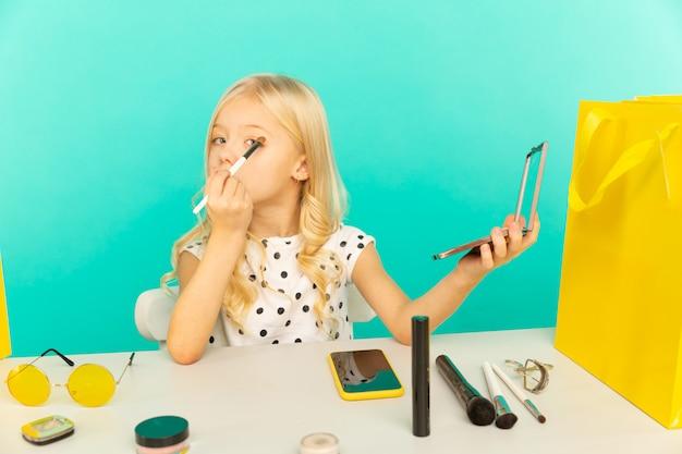 Ładna dziewczyna w domu, mówiąc przed kamerą na vlog. małe dziecko pracujące jako bloger, nagrywające samouczek wideo do internetu.