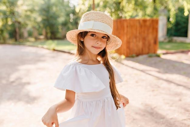 Ładna dziewczyna w dużym słomkowym kapeluszu bawi się białą sukienką podczas pozowania w parku z drewnianym płotem. portret ślicznej kobiety nosi na drodze kapturek ozdobiony wstążką.