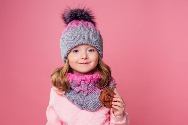 Ładna dziewczyna w dzianym kapeluszu jedzenie świąteczne biscuits.child model dieta różowy tło w studio.