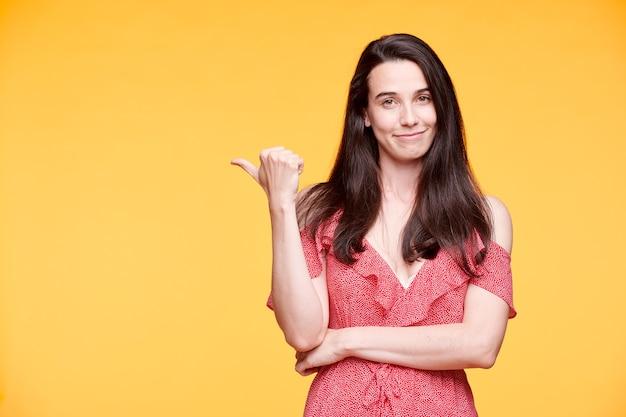 Ładna dziewczyna w eleganckiej czerwonej sukience trzymając ramiona w pasie, wskazując kciukiem na żółtą ścianę