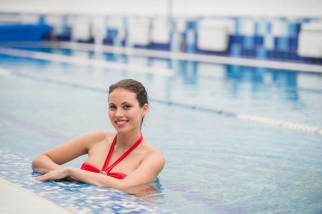 Ładna dziewczyna w fantazyjnych bikni wokół basenu