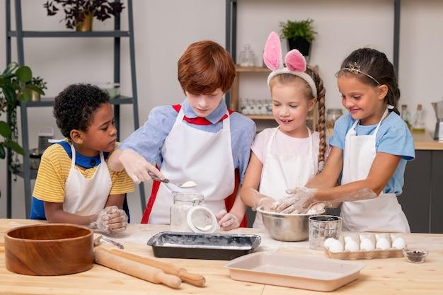 Ładna dziewczyna w fartuchu, trzymająca w dłoniach cyfrowy tablet, stojąc w nowoczesnej kuchni i ucząc swoją młodszą siostrę gotować