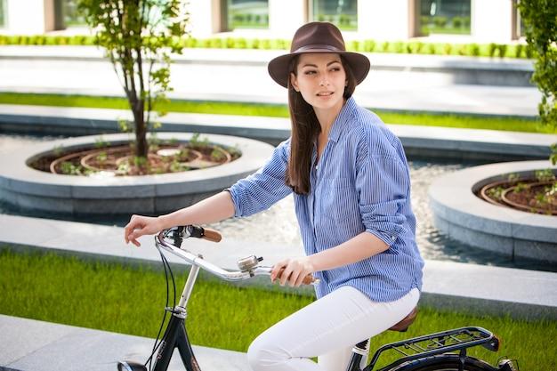 Ładna dziewczyna w kapeluszu jedzie bicykl przy ulicą