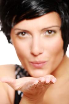 Ładna dziewczyna w krótkich czarnych włosach wysyła buziaki, skup się na dłoni