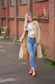 Ładna dziewczyna w krótkich dżinsach i płaszczu spaceru na ulicy po deszczu