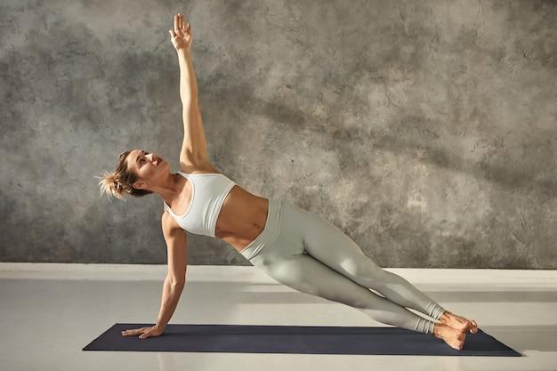 Ładna dziewczyna w legginsach i krótkim topie stojąca w bocznej desce z jednej strony na siłowni, trenująca rdzeń ciała i równowagę, wzmacniająca mięśnie brzucha. atrakcyjna kobieta robi deskowanie ćwiczenia masy ciała