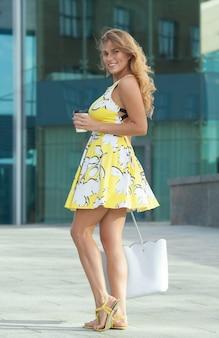 Ładna dziewczyna w letniej sukience na ulicy z poranną kawą