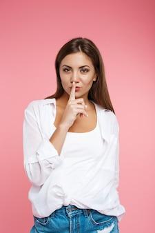 Ładna dziewczyna w letnim wyglądzie prosi o ciszę, patrząc prosto