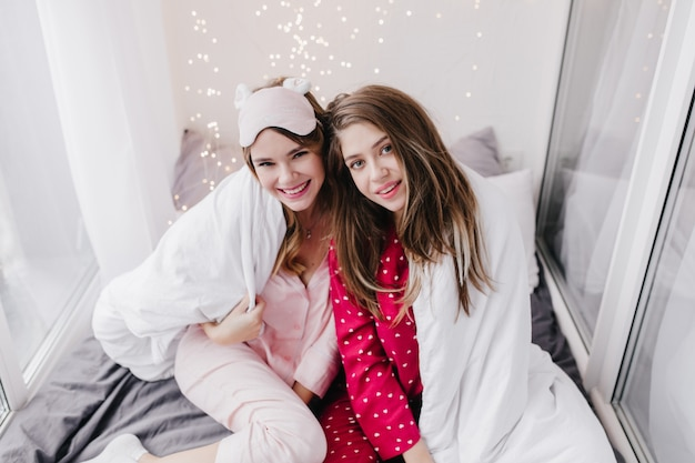 Ładna dziewczyna w modnej różowej masce do spania, siedząc na łóżku w pobliżu koleżanki. zainteresowana ciemnowłosa młoda kobieta w czerwonej bieliźnie nocnej pozuje z kocem.