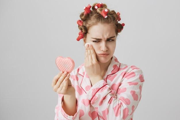 Ładna dziewczyna w nocnej bieliźnie i lokówkach do włosów, patrząc w lustro i zmywalnym makijażem wacikiem