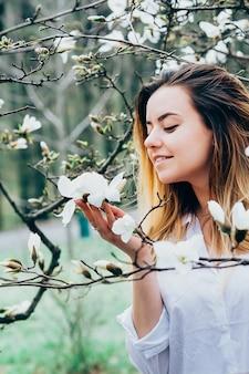 Ładna dziewczyna w ogrodzie lubi kwitnące drzewa magnolii