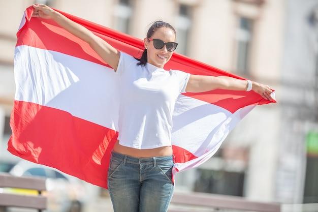 Ładna dziewczyna w okularach przeciwsłonecznych i szeroko otwarte ramiona trzyma austriacką flagę na ulicy.