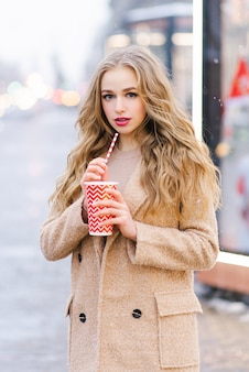 Ładna dziewczyna w płaszczu stoi na ulicy i trzyma czerwono-biały papierowy kubek z tubą...