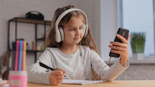 Ładna dziewczyna w słuchawkach studiuje w domu przy użyciu smartfona. uczennica ma lekcję online, pisze w zeszycie, odrabia lekcje.