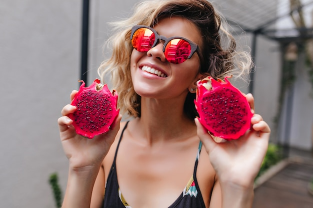 Ładna dziewczyna w stylowe błyszczące okulary, zabawy w letnim kurorcie. cudowna blondynka trzyma czerwoną pitahaya i się śmieje.
