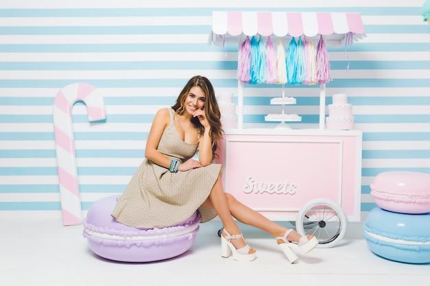 Ładna dziewczyna w sukience retro siedzi w pobliżu sklepu ze słodyczami z wyrazem zadowolonej twarzy dotykając twarzy ręką. portret ładny młoda kobieta ubrana w modne akcesoria sprzedające słodkie ciasta.