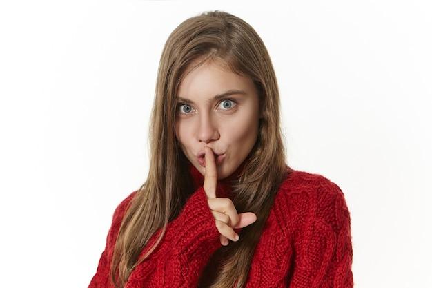 Ładna dziewczyna w swetrze z dzianiny, trzymająca palec wskazujący na ustach i patrząc z figlarnym, tajemniczym wyrazem twarzy, mówi cii, zachowajmy to w tajemnicy. gesty, znaki i mowa ciała