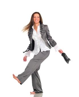 Ładna dziewczyna w szarym garniturze śmieszne pozowanie stojąc na jednej nodze i trzyma buty w rękach. pełnowymiarowe zdjęcie na jasnej ścianie