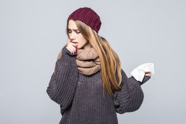 Ładna dziewczyna w szarym swetrze jest przeziębiona, miała grypowy kaszel, ból głowy na szarym