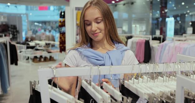 Ładna dziewczyna wybiera ubrania na półkach sklepu po zniesieniu kwarantanny z powodu koronawirusa i pandemii.