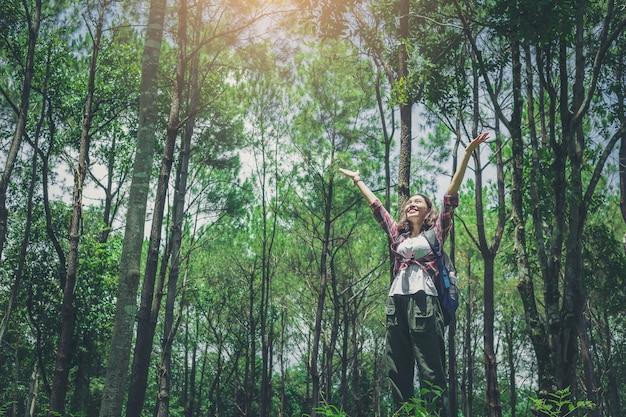 Ładna dziewczyna wycieczkowicz z plecakami otwartymi ramionami cieszyć się przyrodą w dużym lesie.
