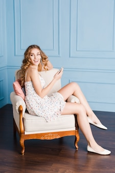 Ładna dziewczyna z blond kręconymi włosami siedzi na fotelu w studio z niebieskimi ścianami. nosi białą sukienkę i buty
