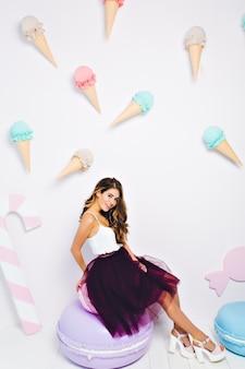 Ładna dziewczyna z błyszczącą fryzurę kręcone spoczywa na krześle ładny makaronik i uśmiechnięty. pełen wdzięku młoda kobieta z wyrazem zadowolonej twarzy pozuje na ścianie ozdobionej kolorowymi lodami i cukierkami.