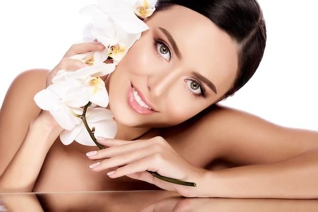 Ładna dziewczyna z brązowymi włosami związanymi z tyłu, czystą, świeżą skórą, dużymi oczami i nagimi ramionami pozuje z białą kwiatową ścianą, zbliżenie.