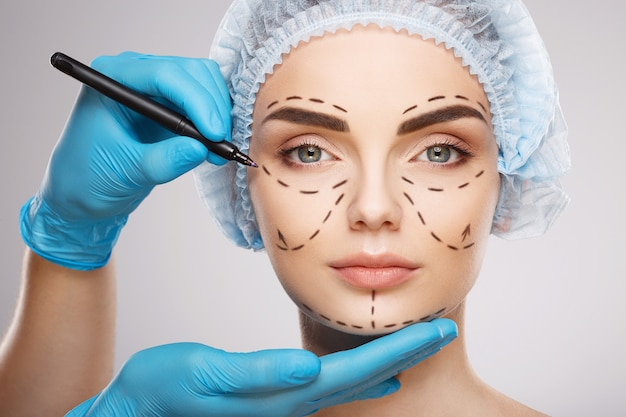 Ładna dziewczyna z ciemnymi brwiami na sobie niebieski medyczny kapelusz na ścianie, ręce lekarza w niebieskich rękawiczkach rysujących linie perforacji na twarzy, koncepcja chirurgii plastycznej.