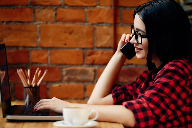 Ładna dziewczyna z czarnymi włosami w okularach siedzi w kawiarni z laptopem, telefonem komórkowym i filiżanką kawy, koncepcja freelance, portret, miejsce na kopię, ubrana w czerwoną koszulę.