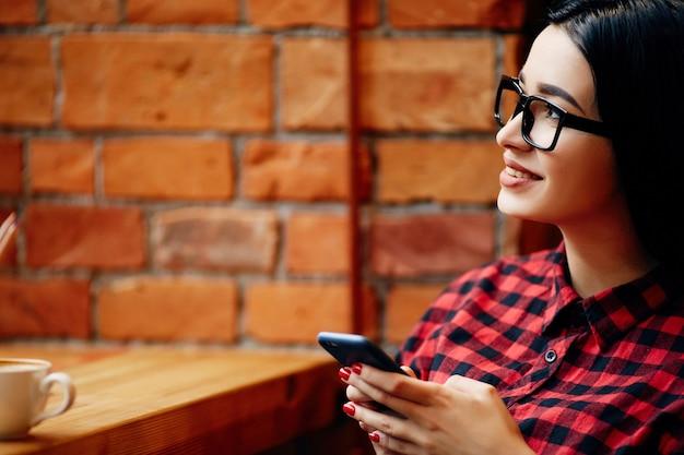 Ładna dziewczyna z czarnymi włosami w okularach siedzi w kawiarni z telefonem komórkowym i filiżanką kawy, niezależna koncepcja, portret, miejsce na kopię, na sobie czerwoną koszulę.