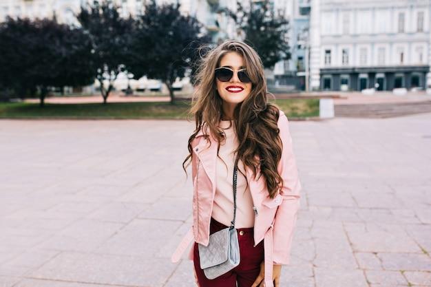 Ładna dziewczyna z długą fryzurą w okularach przeciwsłonecznych chodzi po mieście. nosi winne spodnie, różową kurtkę, uśmiechnięta.