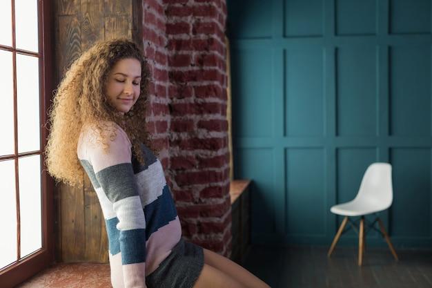 Ładna dziewczyna z długimi kręconymi włosami siedzi na parapecie.