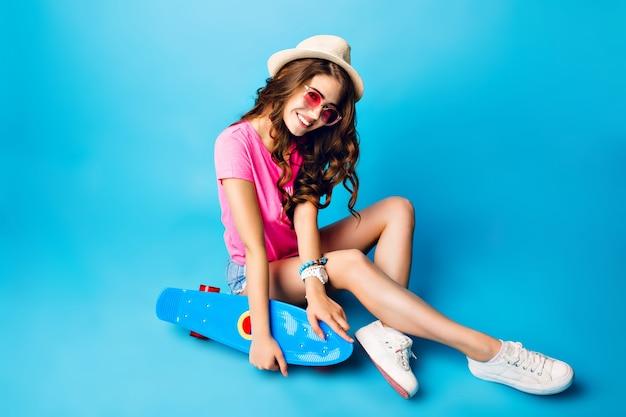 Ładna dziewczyna z długimi kręconymi włosami w kapeluszu, pozowanie na niebieskim tle w studio. nosi szorty, różową koszulkę. siada na podłodze i trzyma niebieską deskorolkę.
