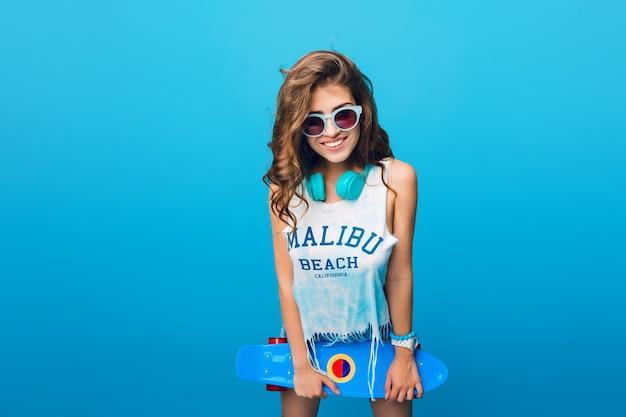 Ładna dziewczyna z długimi kręconymi włosami w okulary na niebieskim tle w studio. nosi szorty, niebieskie słuchawki na szyi, białą koszulkę. trzyma niebieską deskorolkę i uśmiecha się do kamery.