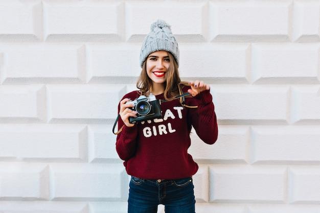 Ładna dziewczyna z długimi włosami na szarej ścianie. nosi dzianinową czapkę, trzyma aparat i przyjaźnie się uśmiecha.