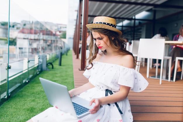 Ładna dziewczyna z długimi włosami siedzi na podłodze na tarasie. nosi białą sukienkę z odkrytymi ramionami, czerwoną szminką i kapelusz. ma laptopa na kolanach i wygląda na zdenerwowaną.