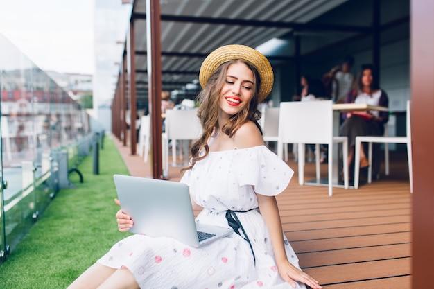 Ładna dziewczyna z długimi włosami siedzi na podłodze na tarasie. nosi białą sukienkę z odkrytymi ramionami, czerwoną szminką i kapelusz. trzyma laptopa na kolanach i uśmiecha się.