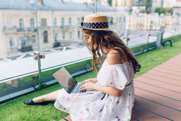 Ładna dziewczyna z długimi włosami siedzi na podłodze na tarasie. nosi białą sukienkę z odkrytymi ramionami i kapelusz. pisze na laptopie na kolanach.