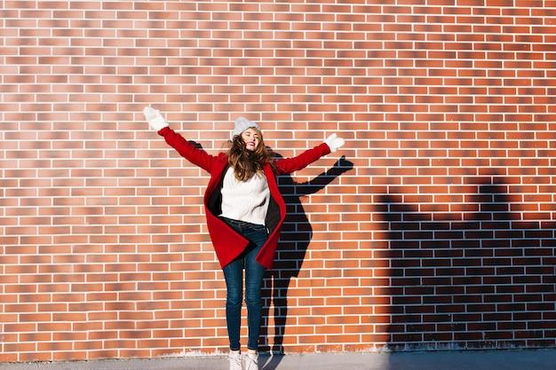 Ładna dziewczyna z długimi włosami w czerwony płaszcz i białe rękawiczki na ścianie na zewnątrz. skacze z zamkniętymi oczami i wspaniałym uśmiechem.