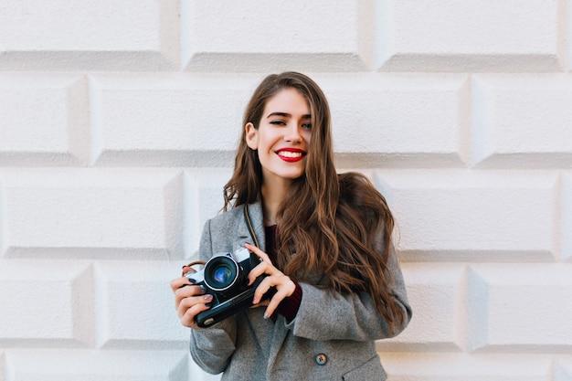 Ładna dziewczyna z długimi włosami w szarym płaszczu na ścianie. trzyma aparat i uśmiecha się z czerwonymi ustami.
