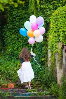 Ładna dziewczyna z dużymi kolorowymi balonami chodząca po schodach na starym mieście