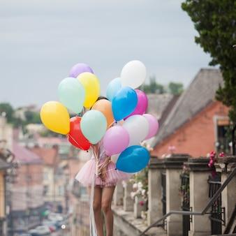 Ładna dziewczyna z dużymi kolorowymi lateksowymi balonami pozuje na ulicy starego miasta