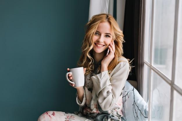 Ładna dziewczyna z falowanymi włosami rozmawia przez telefon i trzymając w ręku kubek, siedząc na parapecie. pokój z niebieską, turkusową ścianą. ubrana w ładną piżamę w kwiaty.