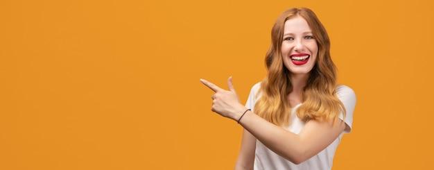 Ładna dziewczyna z falującą rudowłosą, ubrana w białą koszulkę, zaskoczona i wskazująca palcem w bok, pokazuje miejsce na kopię twojej informacji.