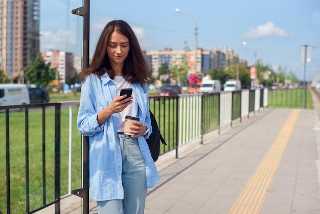 Ładna dziewczyna z filiżanką kawy czeka rano na autobus lub tramwaj na stacji transportu publicznego. młoda kobieta z inteligentnego telefonu monitorowania transportu za pośrednictwem aplikacji.