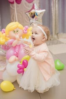 Ładna dziewczyna z kolorowymi balonami i prezentami na przyjęciu urodzinowym
